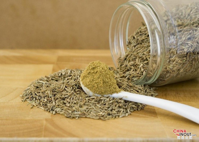 cumin-powder-on-spoon-and-cumin-seeds-spilling-from-a-jar